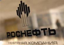 Логотип Роснефти у входа в ее офис в Санкт-Петербурге, 18 октября 2012 года. Государственная Роснефть ведет переговоры с 20 банками о привлечении около $25 миллиардов на поглощение своего конкурента, третьей по размеру нефтекомпании РФ ТНК-BP, при этом окончательный объем займа может возрасти до $35 миллиардов, сообщили Рейтер банкиры. REUTERS/Alexander Demianchuk