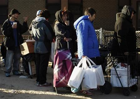 People waiting in line look at a distribution site in the Coney Island section of Brooklyn, New York, November 6, 2012. The people in the coastal communities of Long Island and Queens in New York were among the hardest hit by Superstorm Sandy. Now they are suffering new blows because of the inability of their power utility to restore electricity quickly. REUTERS/Brendan McDermid