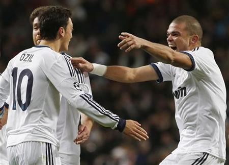 Real Madrid's Pepe (R) and Xabi Alonso (L) celebrate with team mate Mesut Ozil after he scored a last minute equalizing goal against Borussia Dortmund during their Champions League Group D soccer match at Santiago Bernabeu stadium in Madrid November 6, 2012. REUTERS/Juan Medina