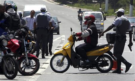 A policeman searches a motorcyclist at a checkpoint in Sao Paulo October 8, 2012. Picture take October 8, 2012. REUTERS/Paulo Whitaker/Files