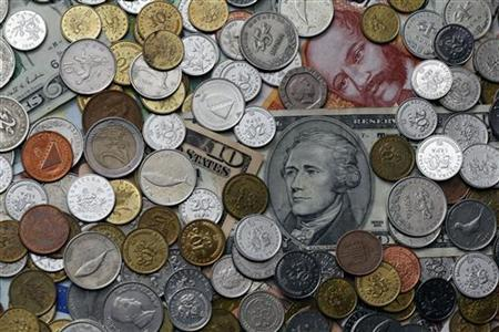A picture illustration of coins from various countries laying on 10 Dollar and 100 kuna banknotes, taken in Zagreb January 18, 2011. REUTERS/Nikola Solic