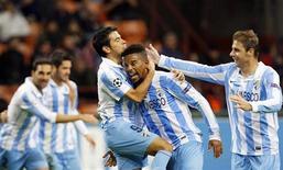 El Málaga y el Oporto se convirtieron en los primeros equipos en alcanzar los octavos de final de la Liga de Campeones al asegurar el martes su pase de la etapa de grupos, mientras que el Real Madrid empató 2-2 en casa ante el Borussia de Dortmund. En la imagen, Eliseu celebra un gol del Málaga con Javier Saviola y Joaquín en San Siro, el 6 de noviembre de 2012. REUTERS/Alessandro Garofalo