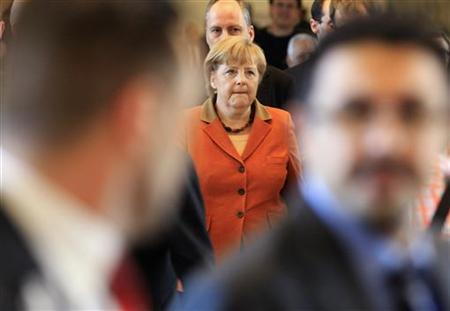 Germany's Chancellor Angela Merkel (L) walks into the European Parliament in Brussels November 7, 2012. Merkel is holding meetings with several political groups at the European Parliament on Wednesday. REUTERS/Yves Herman (BELGIUM - Tags: POLITICS)