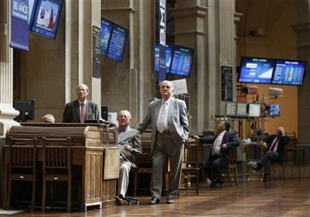 Traders look at electronic boards at the Madrid stock exchange June 22, 2012. REUTERS/Andrea Comas/Files