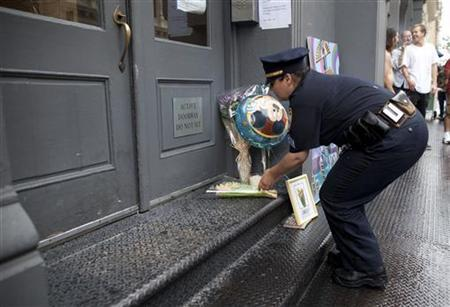 A New York police officer places flowers outside the family home of Etan Patz, who disappeared 33 years ago in New York May 26, 2012. REUTERS/Andrew Kelly