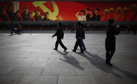 People walk in front of a screen showing propaganda displays near the Great Hall of the People at Beijing's Tiananmen Square, November 7, 2012. REUTERS/Carlos Barria