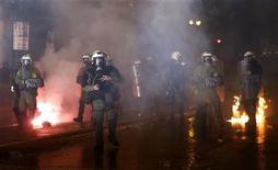 <p>Un grupo de policías antidisturbios avanza entre una columna de gases lacrimógenos y bombas incendiarias durante unos disturbios en Atenas, nov 7 2012. La policía griega empleó gases lacrimógenos y camiones hidrantes para dispersar a miles de manifestantes que abarrotaron la plaza frente al Parlamento de Atenas, en una imponente muestra de descontento contra los legisladores que estaban debatiendo un plan de medidas de austeridad. REUTERS/Yannis Behrakis</p>