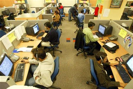 Engineers attend to calls from abroad inside a call center in Gurgaon on the outskirts of New Delhi December 3, 2003. REUTERS/Kamal Kishore/Files