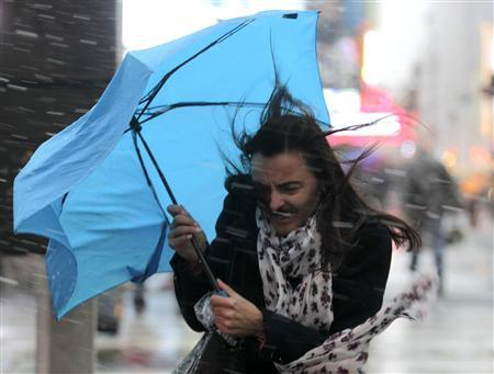 A woman struggles with her umbrella in the wind and snow in New York, November 7, 2012. A wintry storm dropped snow on the Northeast and threatened to bring dangerous winds and flooding to a region still climbing out from the devastation of superstorm Sandy. REUTERS/Brendan McDermid
