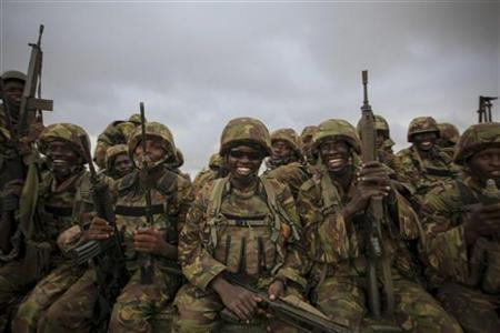 Troops from the Kenyan Contingent of the African Union Mission in Somalia (AMISOM) sit on the back of a flat-bed military truck as they begin an advance on the Somali port city of Kismayu, in this handout photograph taken October 2, 2012 by the African Union-United Nations Information Support Team and released October 3, 2012. REUTERS/African Union-United Nations Information Support Team/Stuart Price/Handout