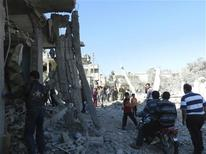 Residents walk among damaged buildings after a Syrian Air Force fighter jet loyal to Syria's President Bashar al-Assad fired missiles at Houla, near Homs, November 6, 2012. Picture taken November 6, 2012. REUTERS/Misra Al-Misri/Shaam News Network/Handout
