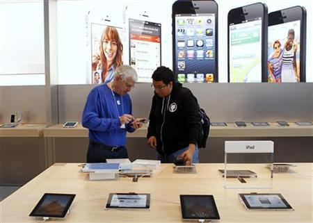 A customer is helped by an Apple employee while looking over the iPad mini after the device went on sale at Apple's retail store in Palo Alto, California November 2, 2012. REUTERS/Robert Galbraith