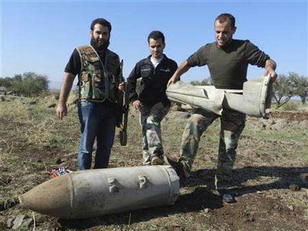 A member of the Free Syrian Army holds an unexploded bomb after a Syrian Air Force fighter jet loyal to Syria's President Bashar al-Assad fired missiles at Houla, near Homs, November 6, 2012. REUTERS/Misra Al-Misri/Shaam News Network/Handout