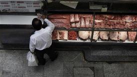 Cliente paga por encomenda em açougue no Mercado Municipal, em São Paulo. Mais uma vez puxado pelos preços dos alimentos, o Índice Nacional de Preços ao Consumidor Amplo (IPCA) acelerou a alta a 0,59 por cento em outubro, após ter subido 0,57 por cento em setembro, segundo o IBGE. 04/02/2012 REUTERS/Nacho Doce