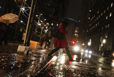 A woman jumps over a puddle during a snow storm in New York's financial district, November 7, 2012. REUTERS/Brendan McDermid