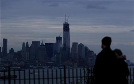 A couple look out at the skyline of New York with most of Lower Manhattan remaining in the dark as they stand in a park along the Hudson River in Weehawken, New Jersey, November 1, 2012. REUTERS/Gary Hershorn