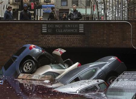 Residents stand over vehicles which were submerged in a parking structure in the financial district of Lower Manhattan, New York October 30, 2012. REUTERS/Adrees Latif
