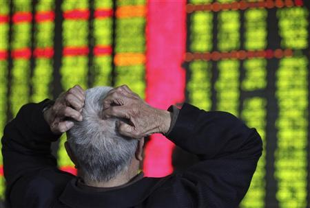 A man scratches his head while looking at an electronic board showing stock information at a brokerage house in Kunming, Yunnan province April 27, 2010. REUTERS/Stringer/Files