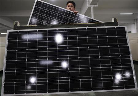 An employee carries a solar panel as he works at a production line at a solar company workshop in Yongkang, Zhejiang province February 23, 2012. REUTERS/Stringer