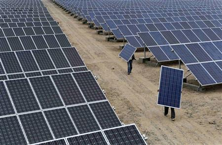 Employees carry solar panels at a solar power plant in Aksu, Xinjiang Uyghur Autonomous Region, in this May 18, 2012 file photo. REUTERS/Stringer/Files