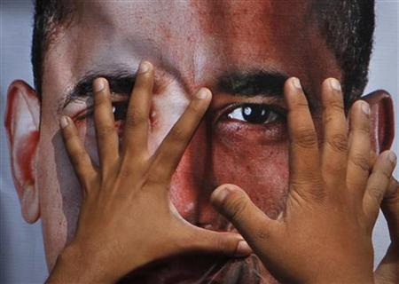A man covers an image of U.S. President Barack Obama, attached to an effigy, during an anti-American rally in Hyderabad September 27, 2011. REUTERS/Akram Shahid/Files