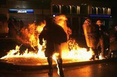 El Gobierno de Grecia consiguió el jueves los votos suficientes en el Parlamento para aprobar unas profundamente impopulares medidas de austeridad que son esenciales para recibir nueva ayuda de los prestamistas internacionales, pese a conflictos internos y violentas protestas a las puertas del Congreso. En la imagen, agentes de policía corren hacia unos manifestantes mientras estallan cócteles molotov en la plaza de Syntagma, Atenas, el 7 de noviembre de 2012. REUTERS/Yannis Behrakis