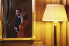 Britain's Prime Minister David Cameron (L) and Germany's Chancellor Angela Merkel are reflected in a mirror as they speak to the media at Downing Street in central London November 7, 2012. Merkel on Wednesday warned Britain not to turn its back on Europe ahead of talks in London with Prime Minister David Cameron aimed at overcoming divisions that threaten to block a European Union budget deal later this month. REUTERS/POOL/Dan Kitwood (BRITAIN - Tags: POLITICS)