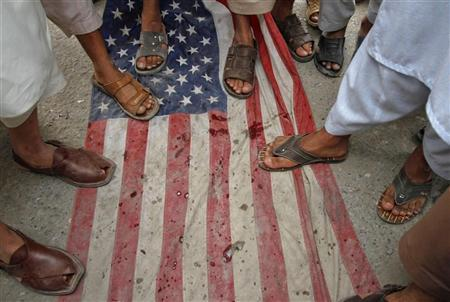 Men step on a U.S flag during an anti-American rally organized by Shabab-e-Milli, the youth wing of the Jamaat-e-Islami party, in Peshawar April 13, 2012. REUTERS/Fayaz Aziz