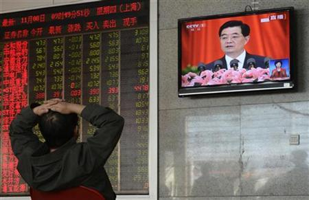 An investor sits in front of an electronic board displaying stock market information and a screen showing Chinese President Hu Jintao delivering a speech during the opening ceremony of the 18th National Congress of the Communist Party of China, at a brokerage house in Taiyuan, Shanxi province, November 8, 2012. Chinese shares fell the most in almost two weeks on Thursday, tracking an Asia-wide drop in riskier assets, with energy stocks the biggest losers after oil prices dived 4 percent overnight. The fall came as Chinese President Hu Jintao vowed reforms to make the currency and interest more market-based, boost overseas investments and plough more state funds into industry as part of plans to keep GDP on track to double in size by 2020, in remarks prepared for delivery at the Communist Party Congress meeting. REUTERS/Stringer (CHINA - Tags: POLITICS BUSINESS) CHINA OUT. NO COMMERCIAL OR EDITORIAL SALES IN CHINA