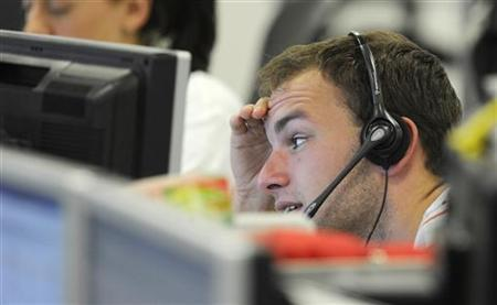 A trader checks screen data at the IG Index trading floor in London June 11, 2011. REUTERS/Paul Hackett/Files