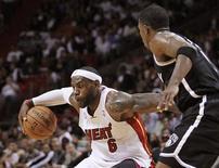 Miami Heat, el actual campeón del título de la NBA, dejó sin aliento a su oponente consecutivo venciendo a Brooklyn por 103-73 el miércoles. En la imagen, de 7 de noviembre, LeBron James de Miami se mueve ante Joe Johnson de los Nets en el partido disputado en Miami, Florida. REUTERS/Andrew Innerarity