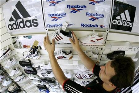 Tobias Hosemann arranges sports shoes in his store in the northern German town of Hamburg August 3, 2005. REUTERS/Christian Charisius/Files