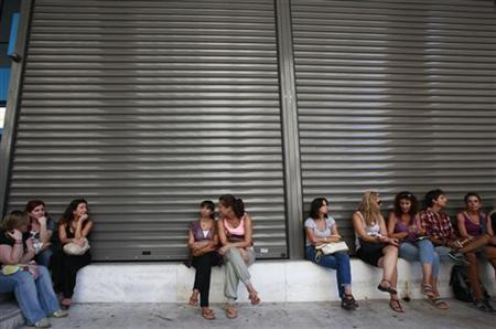 Employees of Hellenic Postbank sit outside the lender's headquarters during a strike against its privatization in Athens September 7, 2012. REUTERS/John Kolesidis
