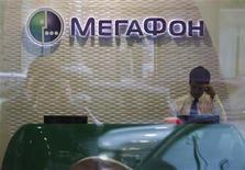 Сотрудник Мегафона в магазине компании в Москве 4 сентября 2012 года. Российский телекоммуникационный оператор связи Мегафон, готовящийся к IPO в Лондоне, в третьем квартале 2012 года увеличил чистую прибыль на 19,6 процента до 14,93 миллиарда рублей, сообщила компания в четверг. REUTERS/Maxim Shemetov