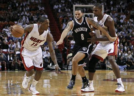 Miami Heat's Mario Chalmers (L) dribbles against Brooklyn Nets' Deron Williams as Heat teammate Chris Bosh (R) looks on in the first half of their NBA basketball game in Miami, Florida November 7, 2012. REUTERS/Andrew Innerarity