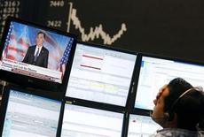 A share trader sits next to a TV showing news on U.S. Republican presidental candidate Mitt Romney, in front of the German share price index DAX board at the German stock exchange in Frankfurt November 7, 2012. REUTERS/Lisi Niesner