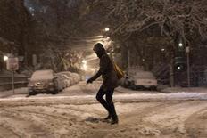 Una donna cammina nella neve durante una tempesta di neve a Jersey City, nel New Jersey. 7 novembre, 2012. REUTERS/Eduardo Munoz