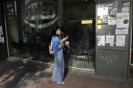 A woman smokes a cigarette outside an unemployment bureau in Athens October 11, 2012. REUTERS/Yorgos Karahalis
