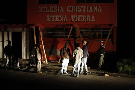 People stand outside a damaged church after a 7.4-magnitude earthquake in San Pedro Sacatepequez in the San Marcos region, about 250 km (120 miles) south of Guatemala City, November 7, 2012. REUTERS/Jorge Dan Lopez