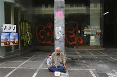 Homem pede dinheiro em frente a lojas fechadas no centro de Atenas. A taxa de desemprego na Grécia subiu pelo 39o mês consecutivo e atingiu a marca recorde de 25,4 por cento em agosto, mais que o dobro da média de 11,5 por cento da zona do euro. 13/09/2012 REUTERS/Yannis Behrakis
