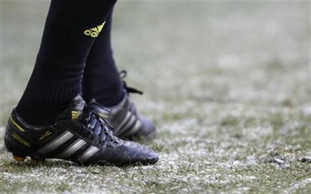 The shoes of a line referee are seen on the partly frozen field during FC Sion's Swiss Super League soccer match against FC Basel in Basel February 5, 2012. REUTERS/Christian Hartmann (SWITZERLAND - Tags: SPORT SOCCER)