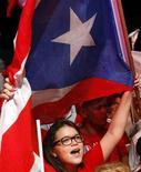 Сторонники Народно-демократической партии Пуэрто-Рико с флагом страны в Сан-Хуане 6 ноября 2012 года. Большинство жителей Пуэрто-Рико поддержали идею вступления в состав США в качестве нового штата на референдуме, прошедшем в среду. REUTERS/Ana Martinez