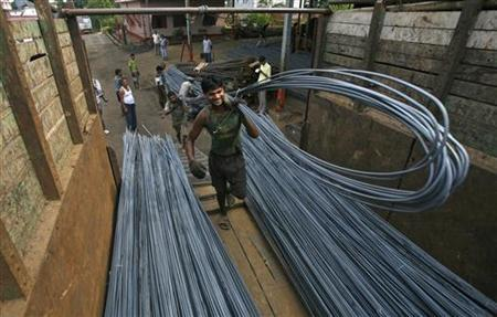 Labourers load iron rods onto a vehicle at a steel factory on the outskirts of Agartala, November 1, 2012. REUTERS/Jayanta Dey/Files