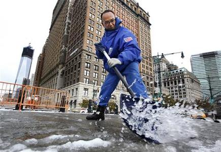 Gilber Hernandez clears snow from a sidewalk in New York's financial district, November 8, 2012. REUTERS/Brendan McDermid
