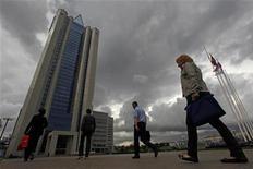 Люди идут к зданию штаб-квартиры Газпрома в Москве 29 июня 2012 года. Крупнейший в мире производитель газа Газпром, чьи финансы в 2012 году серьезно пострадали от падения спроса на европейском рынке, обещает сокращение капзатрат в 2013 году, что поможет ему сохранить долю дивидендных выплат. REUTERS/Maxim Shemetov