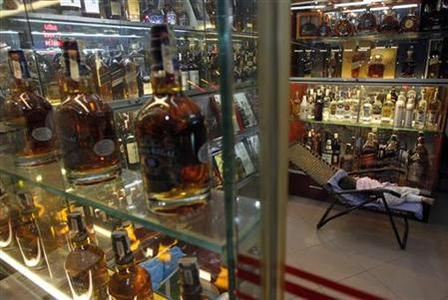 A child sleeps at a shop selling whisky in Hanoi June 6, 2012. REUTERS/Kham/Files