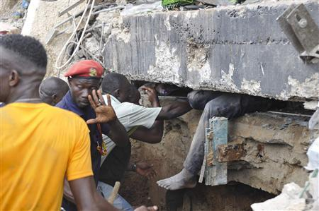 Rescue workers look for survivors from the debris of a collapsed building rented by Melcom Ltd, which runs Ghana's largest chain of retail department stores, in Accra November 7, 2012. REUTERS/Stringer