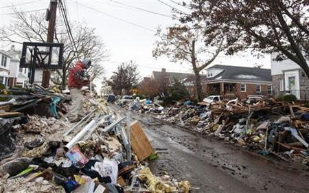 A worker deposits steel onto the top of a pile of debris stacked up outside of homes damaged from flooding that inundated the area during hurricane Sandy in the Queens borough neighborhood of Belle Harbor, New York, November 8, 2012. REUTERS/Lucas Jackson