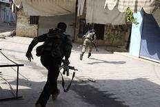 Members of the Free Syrian Army run to avoid a sniper during clashes with pro-government forces in Harem town, Idlib Governorate in this October 30, 2012 file photo. REUTERS/Asmaa Waguih/Files