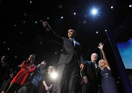 U.S. President Barack Obama gestures onstage during his election night victory rally in Chicago November 7, 2012. Beside Obama are Vice President Joe Biden (2nd R) and Biden's wife Jill Biden. REUTERS/Jason Reed